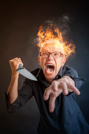 Infuriated angry senior woman slaying, holding a kitchen knife, about to kill someone, her head is burning