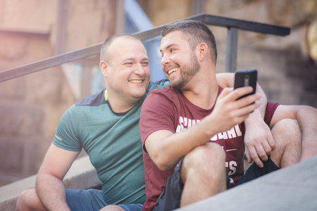 Cute gay couple chatting about online content on their phone Foto de archivo