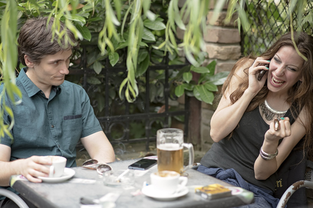 Young men is bored and stressed with his companion having too much fun on the phone, ignoring him completely