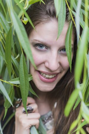 Cheerful young beautiful woman smiling through vibrant green willow branches, enjoying nature and sunny day
