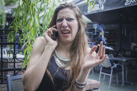 Young attractive woman making a disgusting face while talking on her cell phone, receiving awful news Stok Fotoğraf - 96354504