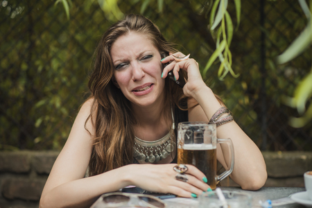 Heart broken girl crying over her cellphone, drunk, drinking a beer in a bar