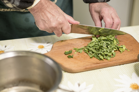 Elderly man, a domestic cook, cutting small pieces of green vegetable, borecole, to prepare for lunch