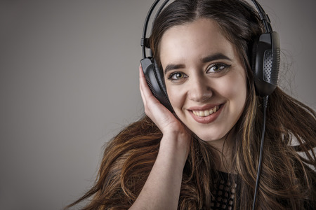 Young woman holding earphones, listening to her favourite music and smiling