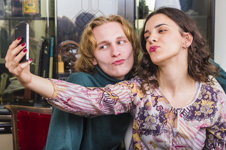 Young cute couple taking a goofy and funny selfie, making duck faces