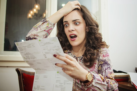 Shocked young woman cant believe the amount of money on her electricity, cable or credit  card bills