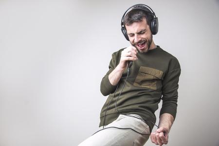 Young man dancing to the sound of the music, singing karaoke 版權商用圖片