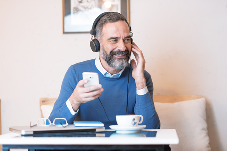 Senior old man listening to his favorite music through big headphones, enjoying the rich sound of the music, hes sitting in a coffee shop Stock Photo