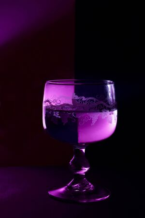 a glass of wine on the black and violet background. Stock Photo - 9777099