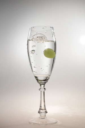 a glass of water and a grape