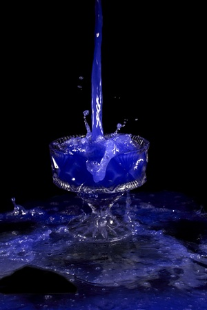 a crystal vase with blue liquid on the black background