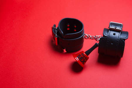 BDSM handcuffs and a bell for on a red background toys for punishment, obedience, and passion. To ring for the beginning of the act of love.