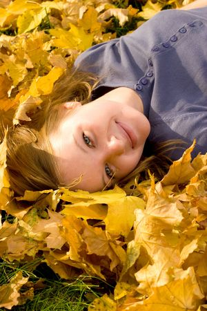 Girl resting in autumn forest, looking at falling leafs photo