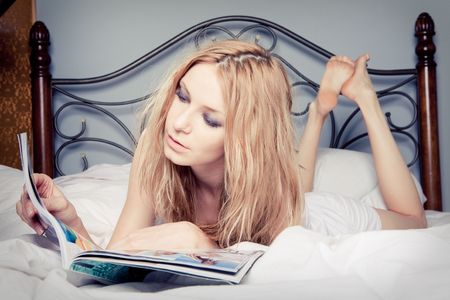 Portrait of beautiful happy woman reading magazine at bedroom photo