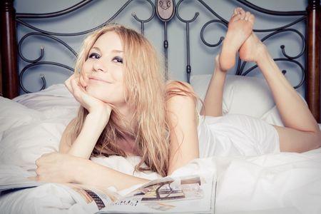 寝室で雑誌を読んで美しい幸せな女の肖像 写真素材