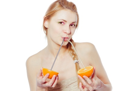 Beautiful young woman drinking juice direct from an orange fruit using a straw  photo