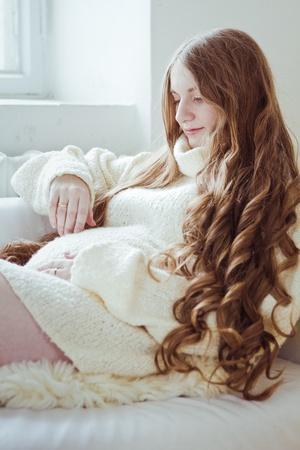 아름 다운 젊은 임신 한 여자 소파에 앉아
