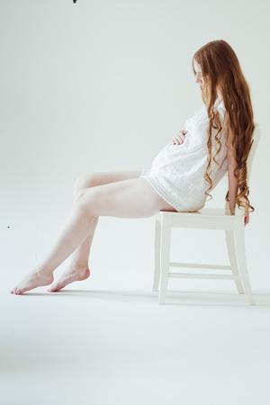 椅子に座って美しい若い妊娠中の女性