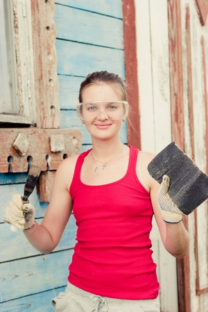 emery paper: Portrait of smiling young woman making cosmetic alterations of house