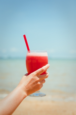 Woman holding fresh fruit cocktail on a tropical island beach photo
