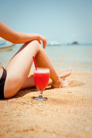 relaxing woman sitting on sand with cocktail