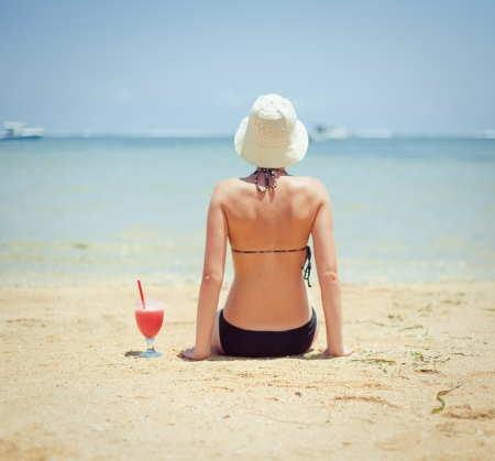 relaxing woman sitting on sand with cocktail Stock Photo - 17395921