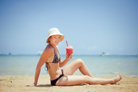 relaxing woman sitting on sand with cocktail  photo
