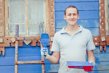 Male painter paints blue wooden wall photo