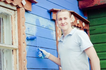 Male painter paints blue wooden wall  Stock Photo - 17481136