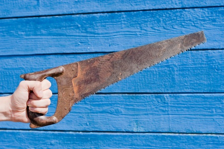 hand with saw on blue wooden background  photo