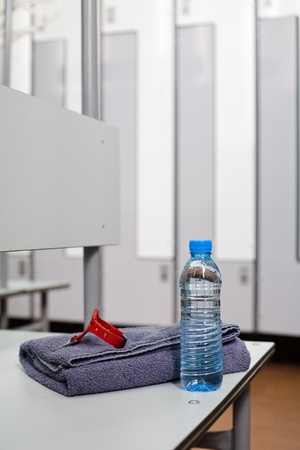 Bottle of water and towel in locker room  photo