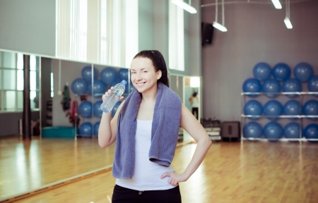 Young woman at the gym drinks water  photo