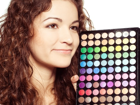 Beautiful girl  with multicolor eyeshadow palette on white background photo