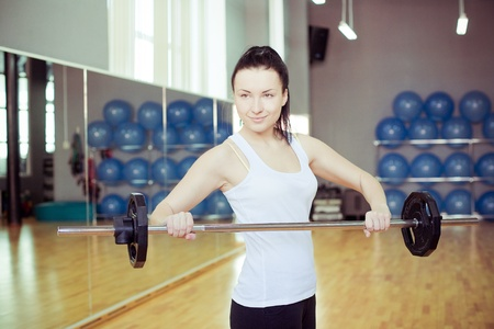 Young woman lifting weights in gym photo