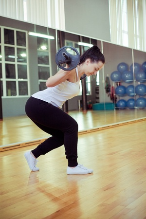 dumb bells: Young woman lifting weights in gym