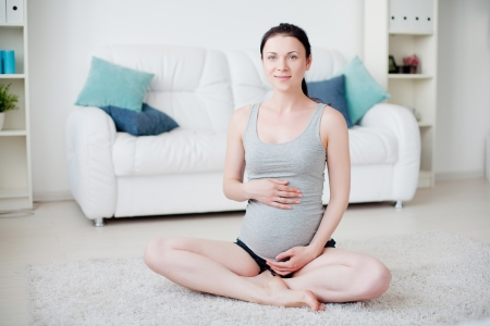 Young pregnant woman do yoga indoors Stock Photo
