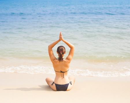 Caucasian woman practicing yoga at seashore photo