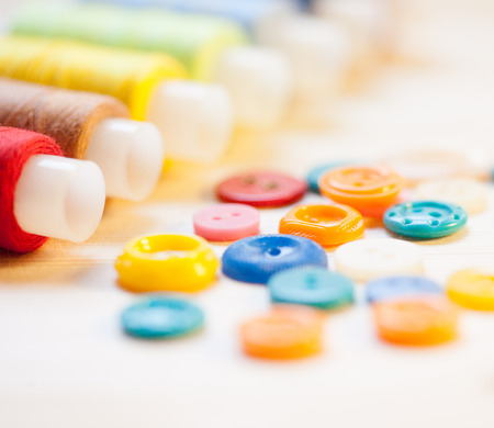 Threads and  colorful buttons  on wooden table photo