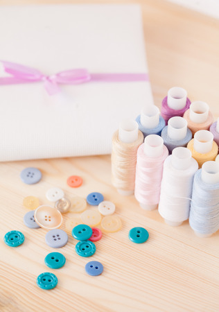 Threads, buttons and fabric on wooden table photo
