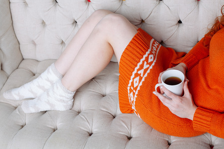 legwarmers: Soft photo of woman on the bed with cup of tea