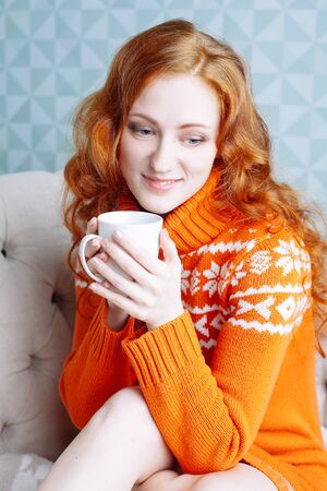 teenager girl: Soft cozy portrait of  woman in warm sweater on the bed with cup of tea in hands