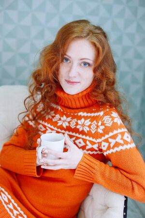 legwarmers: Soft cozy portrait of  woman in warm sweater on the bed with cup of tea in hands