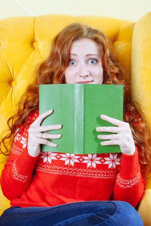 Beautiful shocked young redhair woman reading book