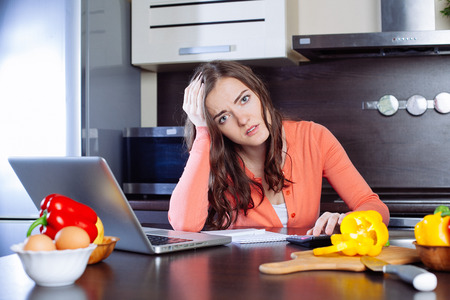 work from home: stressed young woman is doing banking and administrative work holding bills at home Stock Photo