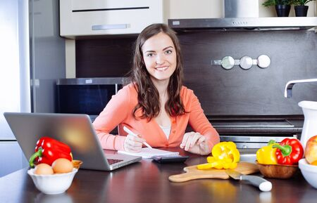 work from home: Happy young woman is doing banking and administrative work holding bills at home