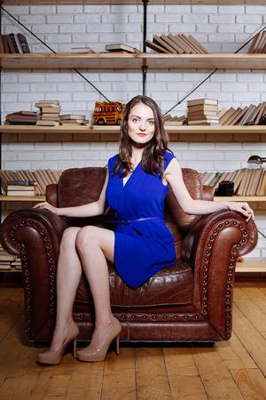 femme brune sexy: Fashion portrait de jeune femme brune de d�tente au fauteuil en cuir en robe bleue