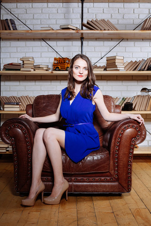 Fashion portrait of young brunette woman relaxing at leather armchair in blue dress