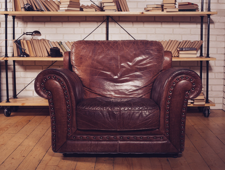 Classic Brown leather armchair in library room Stock Photo