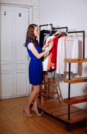 chooses: Young woman chooses clothes in the wardrobe closet Stock Photo