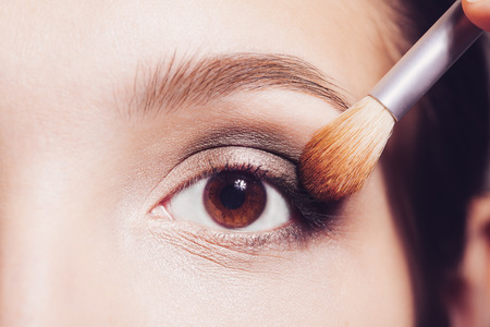 Eye makeup woman applying eyeshadow powder